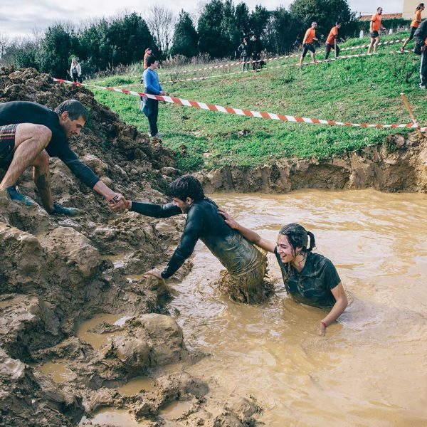 bigstock-Team-helping-to-cross-mud-pit--116872709